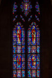 Stained Saints. Multiple Panel Red Blue Yellow Purple and Green Stained Glass Images of Christian Saints In Red Robes Standing with Various Biblical Figures stock photos