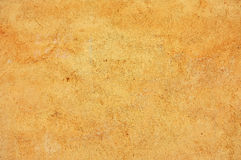 Stained, textured, yellow colored concrete wall Stock Photography