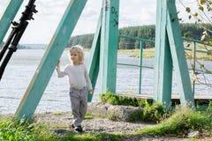 staing在一座老木下垂桥梁的一个愉快的白肤金发的男孩 库存照片