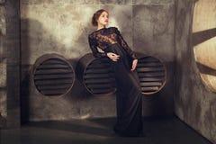 staing在透气附近的黑葡萄酒礼服的女孩用管道输送 骄傲地和周道地看在旁边 库存照片