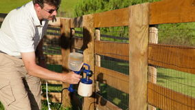 Staining fence. A man is staining wooden fence with electric sprayer stock footage
