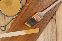 Staining Natural Cedar Wood. Closeup top view of painting tools consisting of hand brush, stir stick, can opener, and paint lid on cedar wooden shingles with top Stock Photo