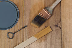 Staining untreated Cedar wood with natural stain. Closeup top view of painting tools consisting of hand brush, stir stick, can opener and paint lid on cedar Stock Image