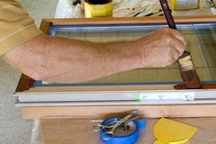 Staining Window Frame #2. Man staining window frame on workbench stock photos