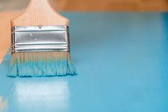 Staining the wooden surface with blue paint using a paint brush.  Stock Photos