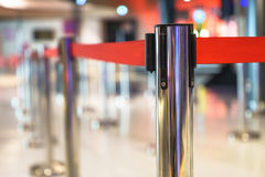 Stainless barricade with red rope on a blurred interior backgrou Royalty Free Stock Photos