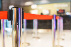 Stainless barricade with red rope on blurred interior background Royalty Free Stock Images