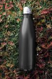 Stainless bottle thermos, black color. On the green grass background. royalty free stock photography