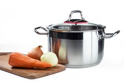 Stainless cooking pot with vegetables on a cutting board stock images