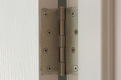 Stainless door hinges on a white door Royalty Free Stock Images