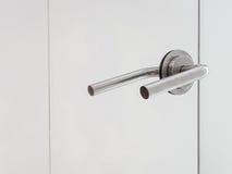 Stainless door knob on the mirror door Royalty Free Stock Photos