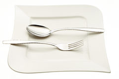 Stainless fork and spoon on plate Stock Photo