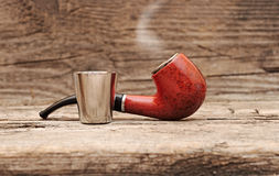 Stainless glass of cognac and tobacco pipe Royalty Free Stock Photo