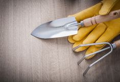 Stainless hand spade rake yellow leather gardening gloves on woo Royalty Free Stock Images