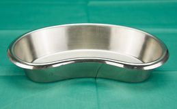 Stainless kidney-shaped bowl on green fabric Royalty Free Stock Images