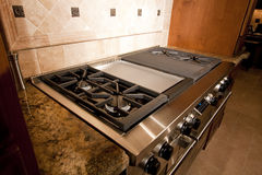 Stainless kitchen oven range and hood. A new home's very expensive kitchen range and hood Royalty Free Stock Image