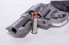 A stainless 357 magnum revolver with a single bullet next to it. Shown on a white background stock photography