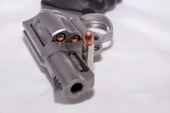 A stainless 357 magnum revolver with a single bullet next to it. Shown on a white background royalty free stock photography