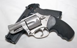 A stainless 357 magnum revolver on top of a black 40 caliber semiautomatic pistol. On a white background royalty free stock photos