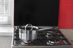 Stainless pan with handle and cover on a gas stove Royalty Free Stock Images