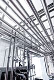 Stainless pipes in factory. With thermometer as background Royalty Free Stock Images