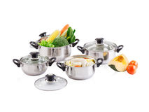 Stainless pots with lids and vegetable Stock Photography