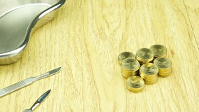 Stainless scalpel and emesis basin with gold coins time lapse stock video footage