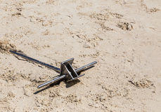 Stainless steel anchor on the sand. Royalty Free Stock Image