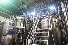 Stainless steel brewing equipment : large reservoirs or tanks and pipes in modern beer factory. Brewery production. Concept, industrial background Stock Image