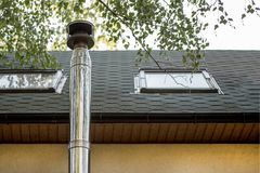 Stainless steel chimney flue on the tile covered roof with windows at country cottage Royalty Free Stock Images