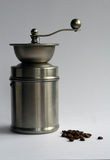 Stainless steel coffee grinder & beans. Stainless steel coffee grinder with coffee beans on a grey background Royalty Free Stock Image