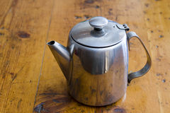 Stainless steel coffee pot. On a wooden surface table top Stock Image