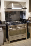 Stainless steel cooker. A stainless steel range cooker with matching extractor hood stock photo