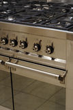Stainless steel cooker. A stainless steel range cooker, section showing hob, ovens and controls stock images