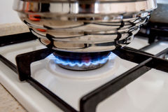 Stainless steel cooking pot on gas stove. Close-up of stainless steel cooking pot on gas stove in contemporary upscale modern home Kitchen Stock Photo