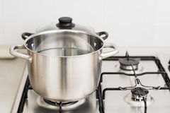 Stainless steel cooking pot on gas stove. Close-up of stainless steel cooking pot on gas stove in contemporary upscale modern home kitchen. Selective focus on Stock Photo