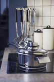Stainless steel cooking pot on a stove and kitchenware stock images
