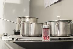 Stainless steel cookware set on induction hob in modern kitchen stock images