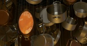 Stainless steel cookware. Hanging and dangling stock footage