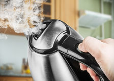 Stainless Steel Electric Kettle in hand on the background of the Royalty Free Stock Images