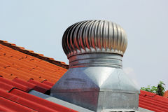 Stainless steel exhaust fan on roof with blue sky Stock Image