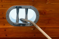 Stainless steel fairlead on a wooden yacht Royalty Free Stock Image