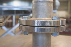 Stainless steel flange. Very shallow depth of field with only the nearest part of the flange in focus with detailed horisontal lines from the lathe visible Royalty Free Stock Photos