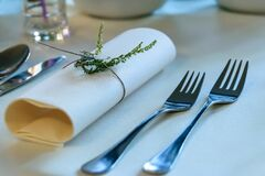 Stainless Steel Fork Beside Rolled Paper Towel With Parsley on Top Stock Photo