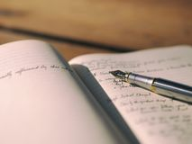 Stainless Steel Fountain Pen on White Notebook With Text Stock Photo