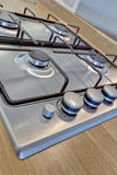 Stainless steel gas hob. Stainless steel domestic gas hob inset within wood effect worktop stock photos
