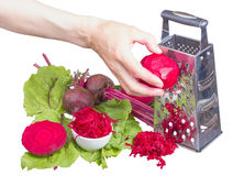 Stainless steel grater and grated beet. Stock Photos