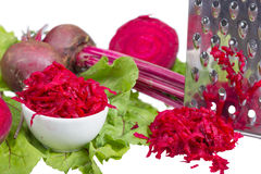 Stainless steel grater and grated beet. Royalty Free Stock Photo