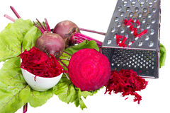 Stainless steel grater and grated beet. Royalty Free Stock Photos