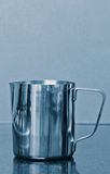 Stainless steel jug. On grey shiny surface Stock Photography